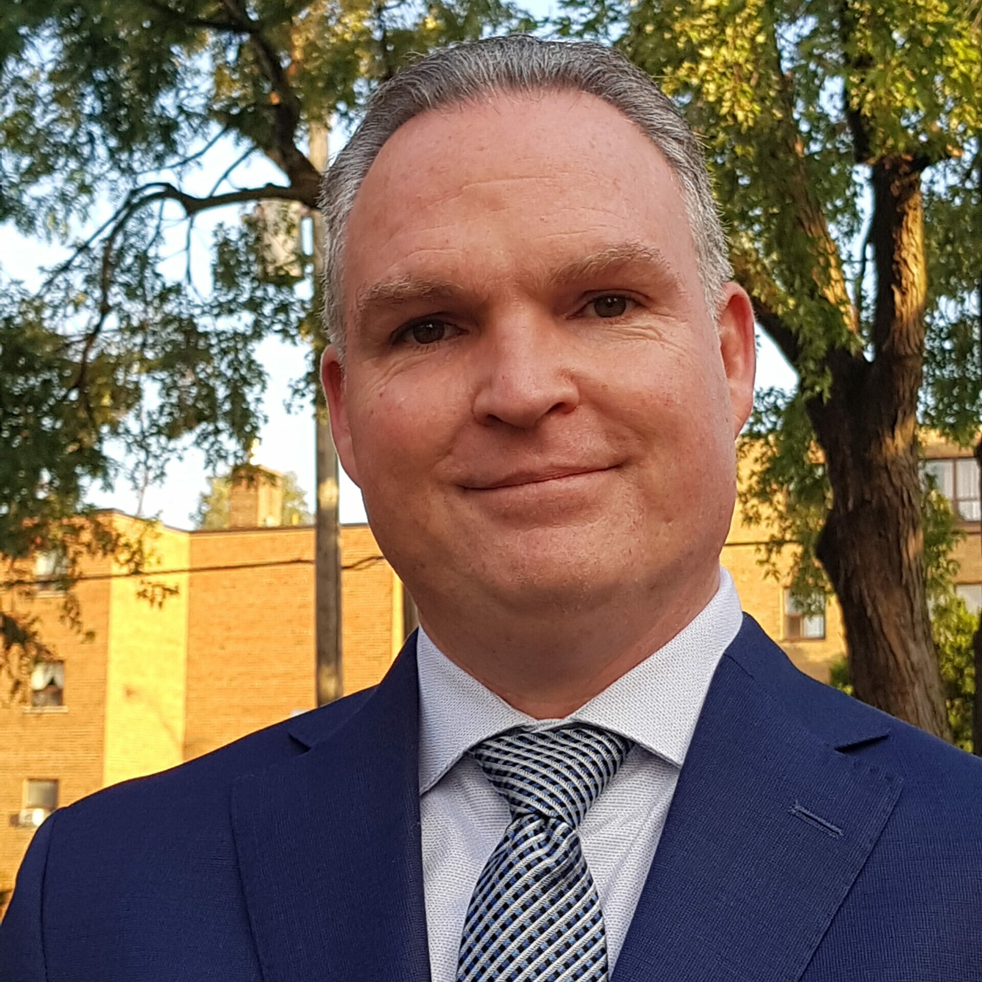 Close-up Shot Of Allan MacDermid In A Dark Blue Suit With Blue Striped Tie Smiling Into Camera, Taken Outside With Trees And A Building Behind Him.